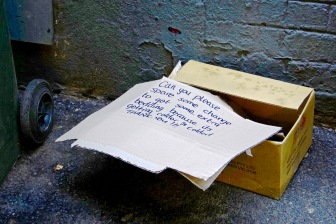 Discarded begging box down a side alley.