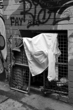 Entrance to a dirty cellar which housed a radio, food cartons and a makeshift bed (up a back lane near the university).